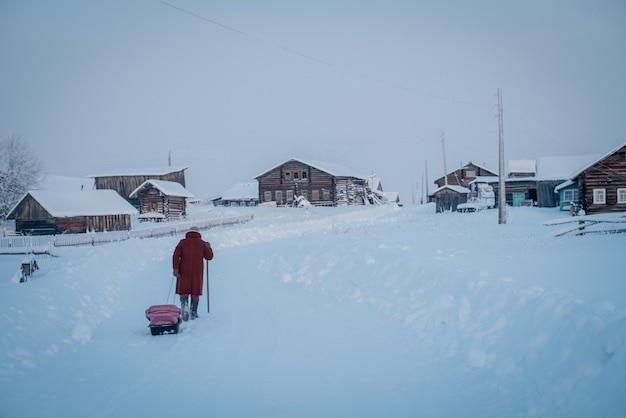 Foto ampla de uma vila e uma pessoa com um casaco vermelho caminhando pela neve espessa em um dia frio