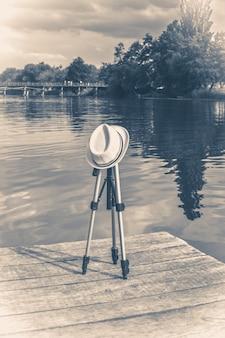 Foto antiga vintage um tripé coberto com um chapéu no cais de madeira do cais
