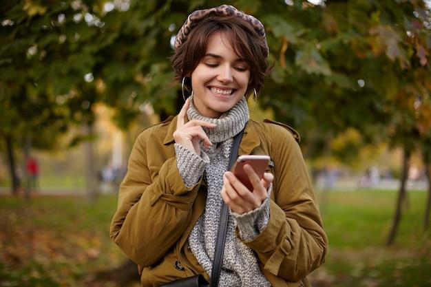 Foto ao ar livre da adorável jovem morena de cabelos curtos com penteado casual segurando um smartphone e olhando alegremente na tela enquanto digita a mensagem, posando sobre o parque desfocado
