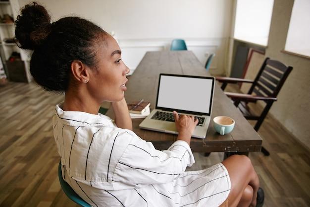Foto ao ar livre da atraente jovem mulher de negócios sentada à mesa com o laptop e falando no celular, olhando para a janela com o rosto pensativo e mantendo a mão no teclado
