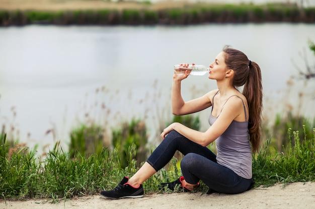 Foto ao ar livre da bela jovem vestindo roupas esportivas e água potável, sentado ao lado de um rio