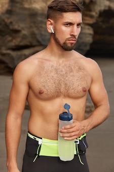 Foto ao ar livre de amante do esporte autoconfiante fazendo exercícios matinais no litoral