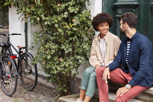 Foto ao ar livre de casal sentado na escada de um café
