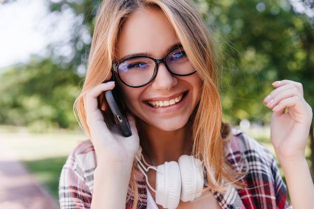 Foto ao ar livre de close-up de uma jovem sonhadora de óculos, falando no telefone. garota rindo em êxtase em fones de ouvido posando em borrão da natureza.