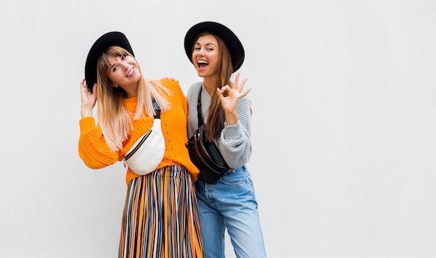 Foto ao ar livre de duas amigas alegres, passando grande tempo juntos posando em branco