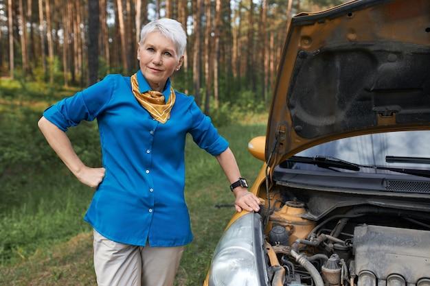 Foto ao ar livre de estressada mulher de meia-idade em pé ao lado de seu carro amarelo com capô aberto, tentando descobrir o problema, esperando por assistência rodoviária, tendo olhar irritado.