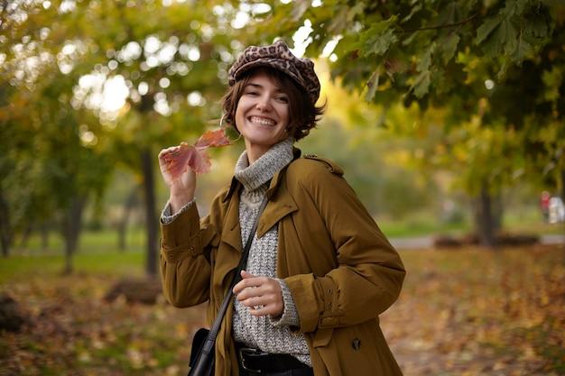 Foto ao ar livre de feliz jovem morena atraente vestida com roupas elegantes, sorrindo amplamente enquanto posava sobre o parque desfocado com uma folha na mão erguida
