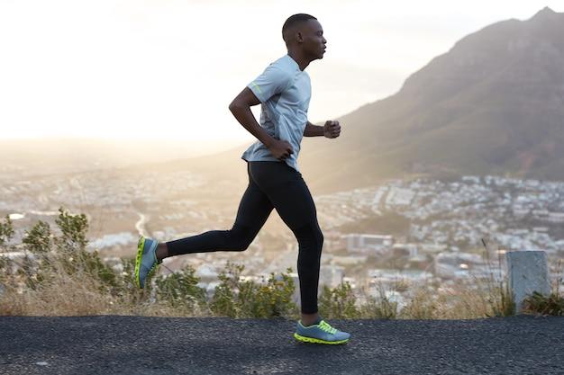 Foto ao ar livre de homem ativo de pele escura correndo pela manhã, tem treinos regulares, vestido com agasalho e tênis confortáveis, concentrado na distância, vê o final à distância.