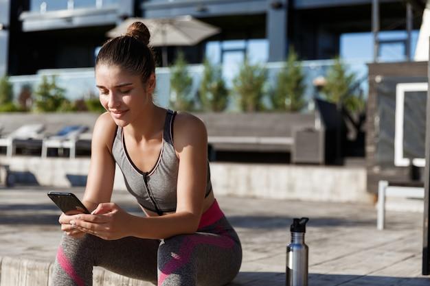Foto ao ar livre de jovem atleta sentada em um banco e olhando para o smartphone