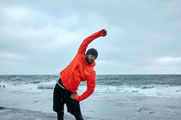 Foto ao ar livre de jovem esportista barbudo de cabelos escuros posando à beira-mar em um frio de manhã cedo, levantando a mão enquanto faz alongamento antes de correr de longa distância à beira-mar