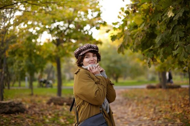 Foto ao ar livre de jovem positiva e atraente de cabelos castanhos, mantendo as mãos no decote enquanto olha com um sorriso encantador, caminhando pelo parque da cidade