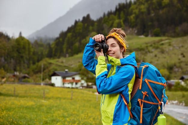 Foto ao ar livre de jovens turistas ativas passeando no campo