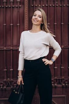 Foto ao ar livre de loira posando em fundo de arquitetura em dia de outono. feche o retrato do estilo de rua da moda. vestindo calças escuras casuais, suéter cremoso e casaco ou jaqueta cinza. conceito de moda.