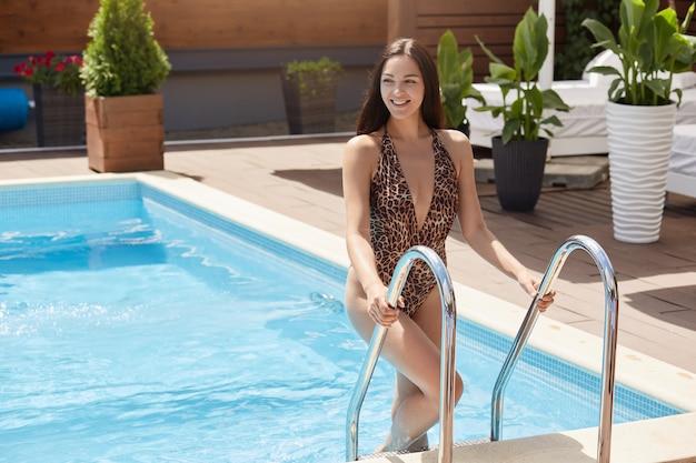 Foto ao ar livre de magro alegre linda morena jovem saindo da piscina, olhando de lado, vestindo roupa de banho de leopardo, sorrindo sinceramente, tempo livre. conceito de férias e recreação.