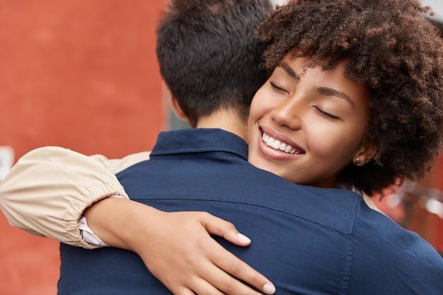 Foto ao ar livre de melhores amigos se abraçando calorosamente