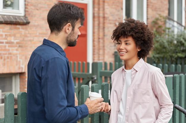 Foto ao ar livre de mestiço mulher e homem se encontrando na rua