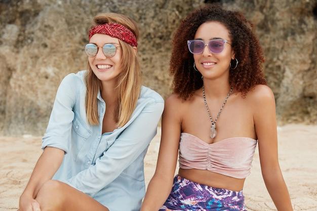 Foto ao ar livre de modelos femininas descontraídas e despreocupadas de diferentes nacionalidades sentadas na praia de areia contra um penhasco, de bom humor enquanto desfrutam da união e do verdadeiro amor mútuo