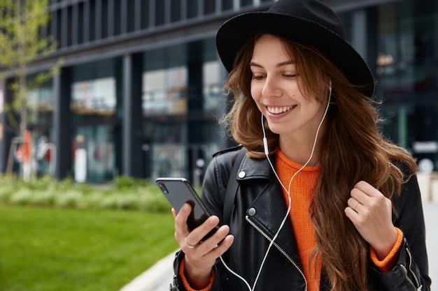 Foto ao ar livre de mulher branca gosta de ouvir música, usa um celular moderno e fones de ouvido, posa no centro da cidade e tem um sorriso cheio de dentes