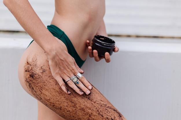 Foto ao ar livre de mulher com esfoliação corporal de café.