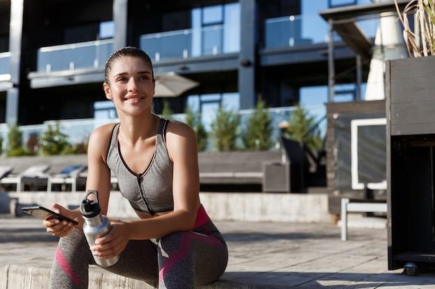 Foto ao ar livre de mulher feliz em forma de fitness sentada no banco após o treino