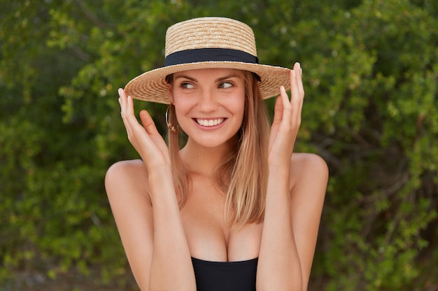Foto ao ar livre de mulher feliz usando chapéu de palha e biquíni preto, olhares com expressão feliz à parte, perceber algo à distância, poses contra vegetação tropical verde mulher elegante na moda