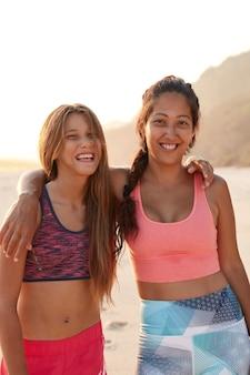 Foto ao ar livre de mulheres amistosas e relaxadas se abraçando durante uma caminhada