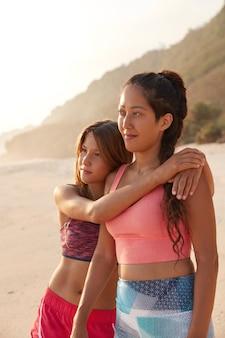 Foto ao ar livre de namoradas calmas se abraçando e curtindo a união durante o descanso de verão à beira-mar