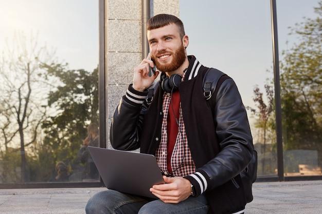 Foto ao ar livre de um cara jovem barbudo vermelho bonito, sentado na rua colocando o laptop no colo, tem conversa telefônica com close frined, gosta de dia de sol e wi-fi grátis na cidade urbana.