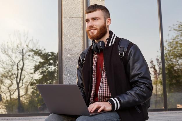 Foto ao ar livre de um jovem barbudo vermelho bonito, sentado na rua colocando o laptop no colo, olhando para a distância e planejando uma viagem para as montanhas.
