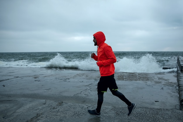 Foto ao ar livre de um jovem desportista vestido com roupas esportivas quentes, correndo pela beira-mar no clima cinza e tempestuoso, concentrado e mantendo as mãos na altura do peito