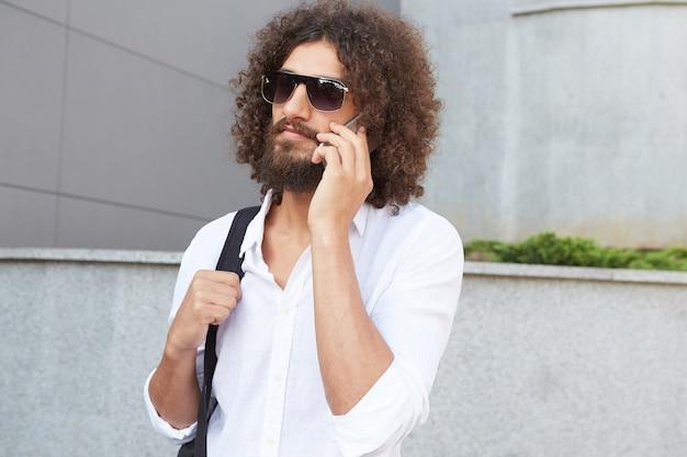 Foto ao ar livre de um jovem e atraente homem barbudo encaracolado com o telefone na mão, caminhando pela rua em um dia ensolarado, vestindo camisa branca e mochila preta