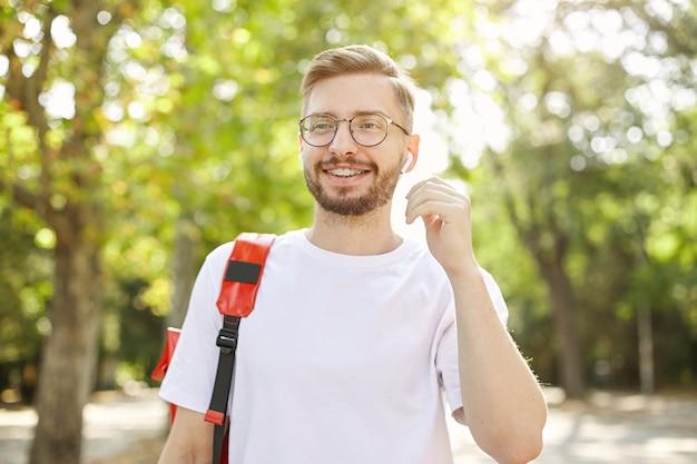 Foto ao ar livre de um jovem homem com barba, usando óculos e camiseta branca, sorrindo amplamente e caminhando no parque, indo puxar o fone de ouvido