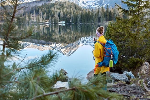 Foto ao ar livre de um jovem viajante com uma bolsa, de costas para a câmera, apreciando montanhas, ar puro e um pequeno lago