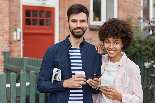 Foto ao ar livre de um lindo casal perto um do outro contra um fundo de tijolo