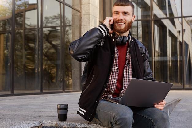 Foto ao ar livre de um rapaz bonito de barba vermelha sentado na rua colocando o laptop no colo, bebendo café enquanto espera pelos amigos com quem fala ao telefone