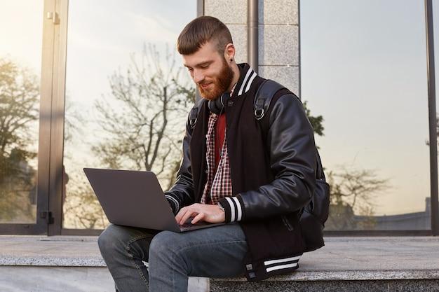 Foto ao ar livre de um rapaz bonito de barba vermelha, sentado na rua colocando o laptop no colo, cria novo conteúdo para seu canal.