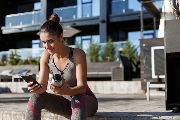 Foto ao ar livre de uma atraente desportista sentada no banco e usando o telefone celular