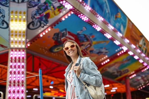 Foto ao ar livre de uma bela jovem de óculos de sol, caminhando pelo parque de diversões em um dia quente, usando um vestido romântico e um casaco jeans, sorrindo sinceramente