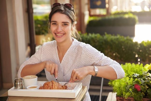 Foto ao ar livre de uma bela jovem morena com roupas de bolinhas brancas cortando croissant com talheres e olhando feliz com um largo sorriso, posando no interior do café
