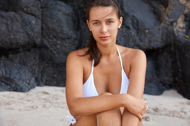 Foto ao ar livre de uma bela turista caucasiana com pele saudável e corpo esportivo