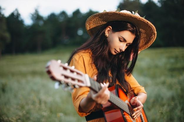 Foto ao ar livre de uma encantadora jovem tocando violão na natureza.