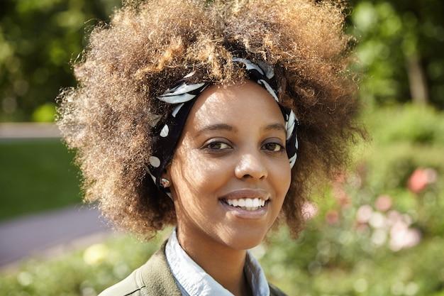 Foto ao ar livre de uma estudante negra sorridente indo para a universidade, passando pelo parque da cidade, parecendo alegre e autoconfiante, aproveitando o dia quente de primavera