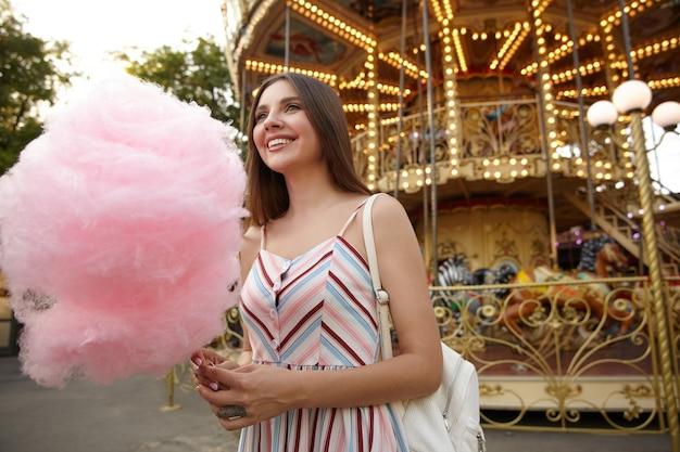 Foto ao ar livre de uma jovem atraente morena de cabelos compridos usando um vestido de verão, posando no carrossel em um dia quente, segurando um pedaço de algodão doce, olhando para o lado com um sorriso sincero
