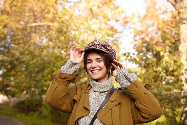 Foto ao ar livre de uma jovem atraente morena de cabelos curtos feliz sorrindo amplamente enquanto olha, posando sobre o jardim da cidade em um dia ensolarado de outono com roupas da moda