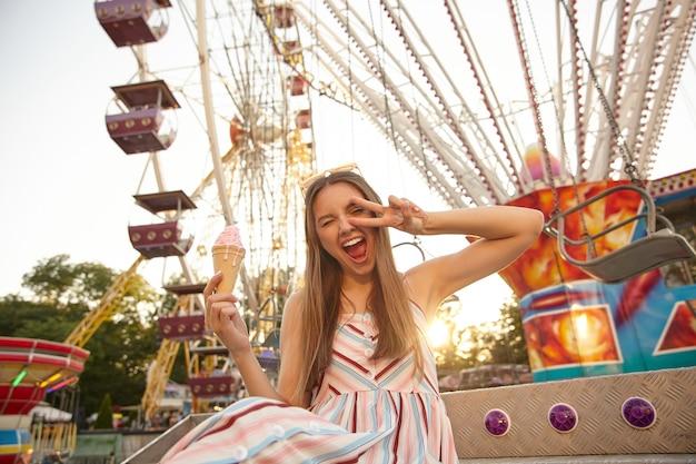 Foto ao ar livre de uma jovem bonita alegre com cabelo castanho sentada em um parque de diversões, sorrindo amplamente com os olhos fechados e levantando a mão em gesto de vitória, comendo sorvete