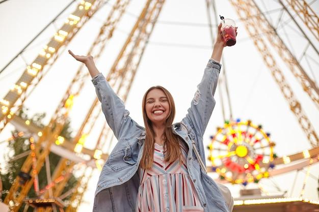 Foto ao ar livre de uma jovem bonita e alegre com longos cabelos castanhos usando um vestido romântico e um casaco jeans da moda, levantando as mãos alegremente e sorrindo amplamente