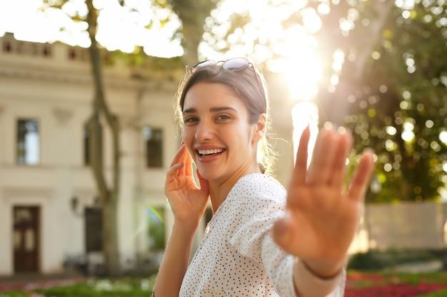 Foto ao ar livre de uma jovem encantadora de cabelos castanhos em roupas de bolinhas brancas, com a palma da mão levantada e sorrindo alegremente