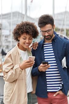 Foto ao ar livre de uma jovem inter-racial amigável e um homem vestido casualmente