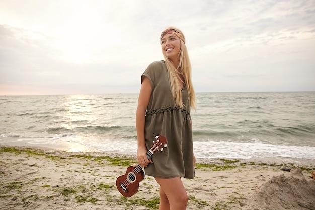 Foto ao ar livre de uma jovem linda de cabelos brancos, vestida com roupas de verão, segurando um ukulele e sorrindo amplamente enquanto olha para o lado, isolada à beira-mar