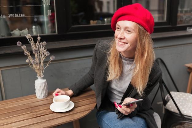 Foto ao ar livre de uma jovem loira atraente com penteado casual, sentada à mesa no café da cidade e esperando por seus amigos, olhando para o futuro alegremente e sorrindo agradavelmente